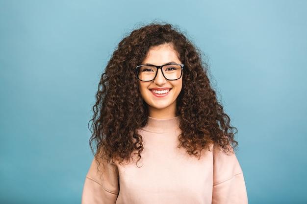 Retrato de uma jovem encaracolado muito sorridente em posar casual isolado em um fundo azul.