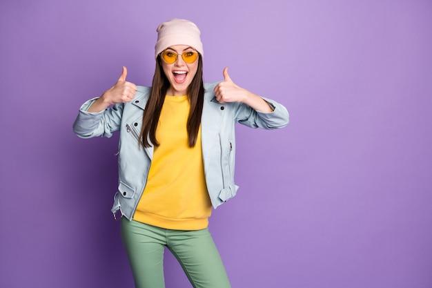 Retrato de uma jovem enérgica e louca aproveite a opção de promoção os anúncios mostram o polegar recomende as decisões de escolha usar calças verde-amarelo isoladas sobre fundo de cor violeta