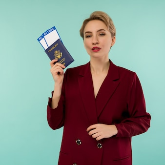 Retrato de uma jovem engraçada com passaporte e cartão de embarque sobre fundo azul. abrindo fronteiras. início das viagens aéreas após uma pandemia.