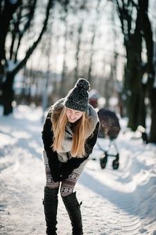 Retrato de uma jovem engraçada feliz pulando e curtindo a neve em um parque de inverno.