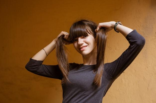 Retrato de uma jovem engraçada, segurando o cabelo nas mãos, olhando para a câmera contra uma parede laranja.