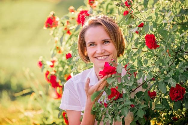 Retrato de uma jovem entre rosas vermelhas sob a luz do sol