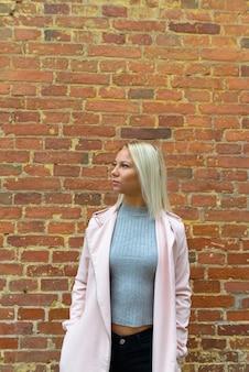 Retrato de uma jovem escandinava loira bonita contra uma parede de tijolos ao ar livre
