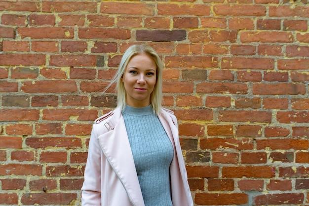 Retrato de uma jovem escandinava loira bonita contra uma parede de tijolos ao ar livre Foto Premium