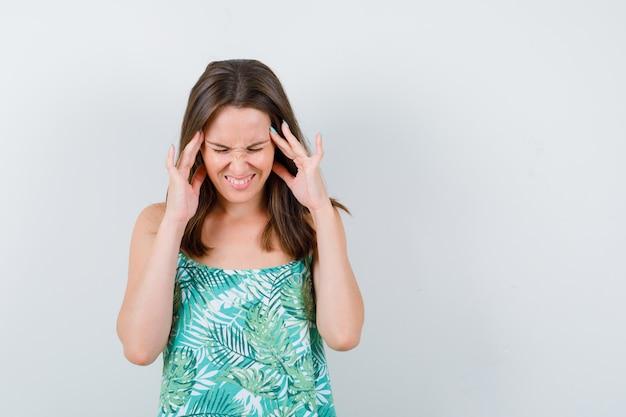 Retrato de uma jovem esfregando as têmporas na blusa e parecendo exausta.