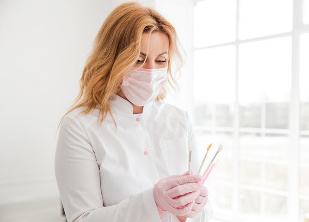 Retrato de uma jovem esteticista atraente com pincel na mão e olhar para ele. cosmetologista segurando ferramentas médicas. clínica ou hospital de beleza.