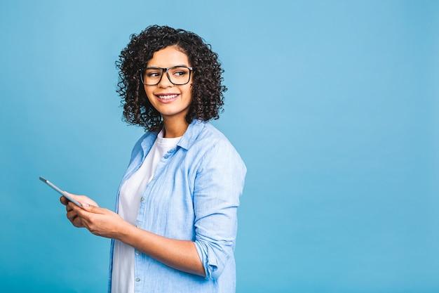 Retrato de uma jovem estudante americana com cabelo encaracolado africano segurando o tablet digital e sorrindo em pé sobre um fundo azul isolado com espaço de cópia para texto, logotipo ou publicidade.
