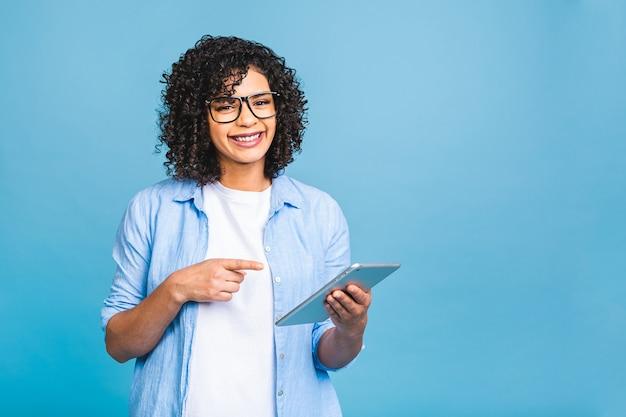 Retrato de uma jovem estudante americana com cabelo encaracolado africano segurando um tablet digital e sorrindo em pé sobre um fundo azul isolado