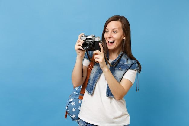 Retrato de uma jovem estudante animada com a boca aberta com mochila tira fotos na câmera fotográfica vintage retrô isolada sobre fundo azul. educação na universidade. copie o espaço para anúncio.