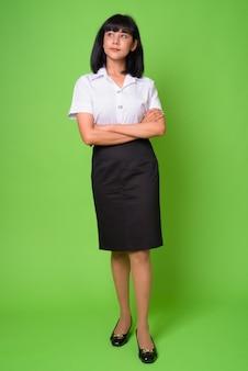 Retrato de uma jovem estudante asiática linda contra uma parede verde