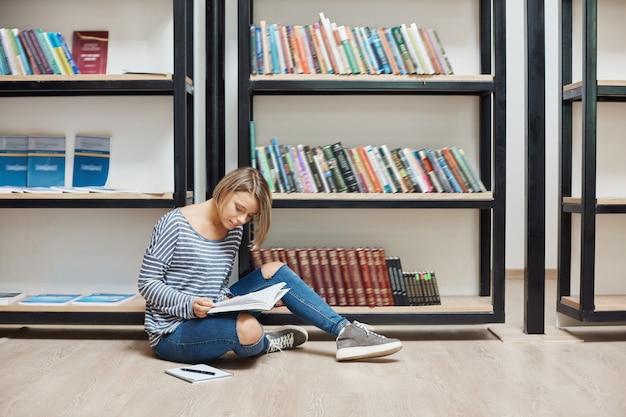 Retrato de uma jovem estudante bonita com cabelo loiro curto em roupas elegantes casuais, sentado no chão na biblioteca moderna perto de prateleiras, lendo livros favoritos, passando o fim de semana em ambiente acolhedor