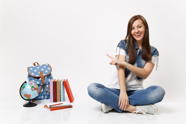 Retrato de uma jovem estudante casual rindo em roupas jeans, sentada, apontando o dedo indicador na mochila do globo, livros escolares isolados