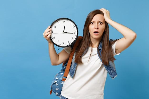 Retrato de uma jovem estudante chocada e irritada com mochila agarrada à cabeça, segure o relógio despertador isolado sobre fundo azul. o tempo está se esgotando. educação na faculdade. copie o espaço para anúncio.