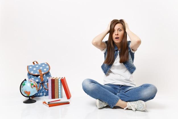 Retrato de uma jovem estudante chocada e preocupada, agarrando-se à cabeça e sentada perto do globo, mochila, livros escolares isolados
