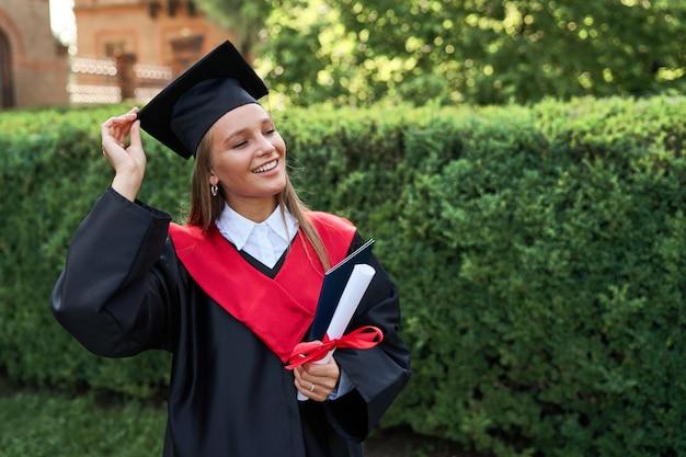 Retrato de uma jovem estudante de pós-graduação bonita com túnica de formatura e diploma