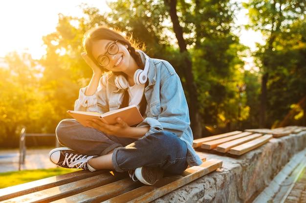 Retrato de uma jovem estudante feliz, alegre e sorridente, usando óculos, sentada ao ar livre no parque natural, ouvindo música com fones de ouvido e lendo um livro