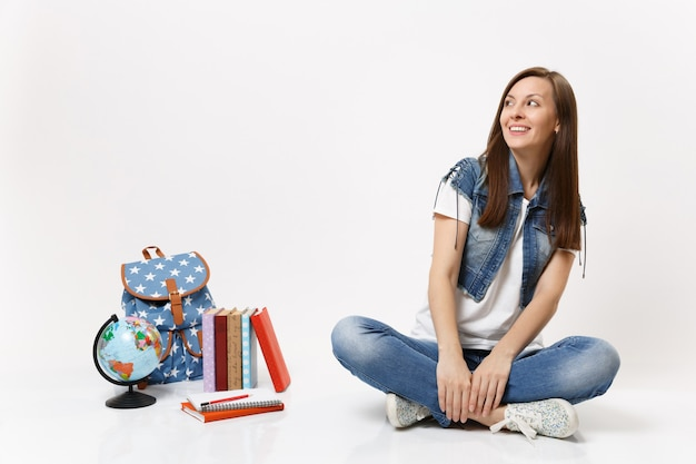 Retrato de uma jovem estudante feliz e sorridente em roupas jeans, olhando para cima, sentada perto do globo, mochila, livros escolares isolados