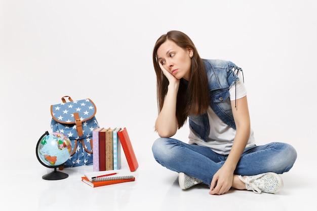 Retrato de uma jovem estudante infeliz em roupas jeans, descansando a bochecha por lado, sentado, olhando para livros escolares de mochila globo isolados na parede branca