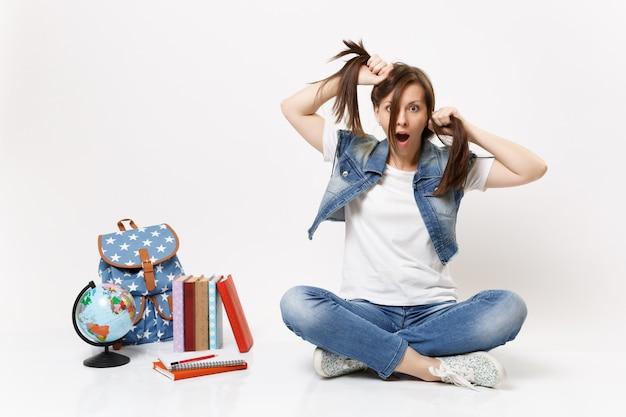Retrato de uma jovem estudante louca e chocada em roupas jeans, segurando um rabo de cavalo, sentada perto do globo, mochila, livros escolares isolados