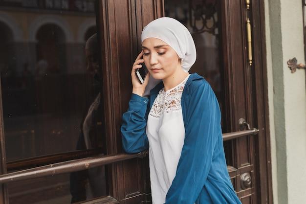 Retrato de uma jovem estudante muçulmana asiática falando ao ar livre ao telefone celular