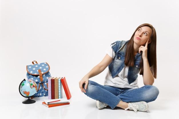 Retrato de uma jovem estudante pensativa em roupas jeans, olhando para cima e sonhando, sentada perto da mochila de livros escolares do globo isolados