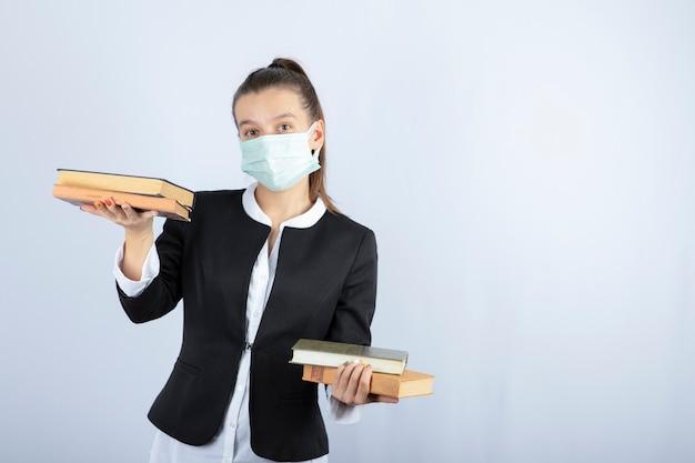 Retrato de uma jovem estudante tentando segurar livros sobre uma parede branca. foto de alta qualidade