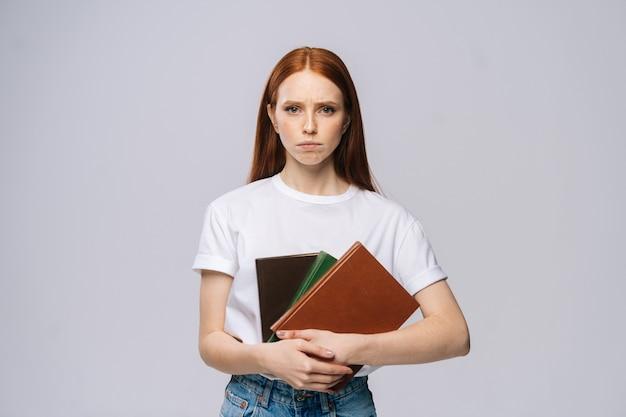 Retrato de uma jovem estudante universitária séria segurando livros e olhando para a câmera