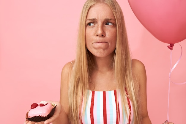Retrato de uma jovem europeia emocional fofa com balão de hélio, seguindo uma dieta restrita e uma expressão facial frustrada e indecisa, quer comer uma sobremesa doce de carboidrato