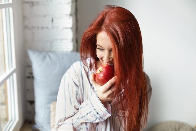 Retrato de uma jovem europeia ruiva encantadora e alegre, vestindo um pijama listrado da moda, olhando feliz, mordendo maçã vermelha madura fresca, comendo frutas no café da manhã, sentada perto da janela no quarto dela