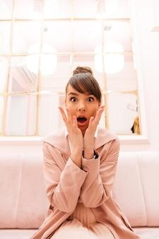 Retrato de uma jovem excitada no casaco sentado