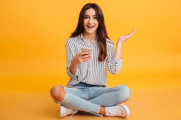 Retrato de uma jovem excitada segurando o telefone móvel