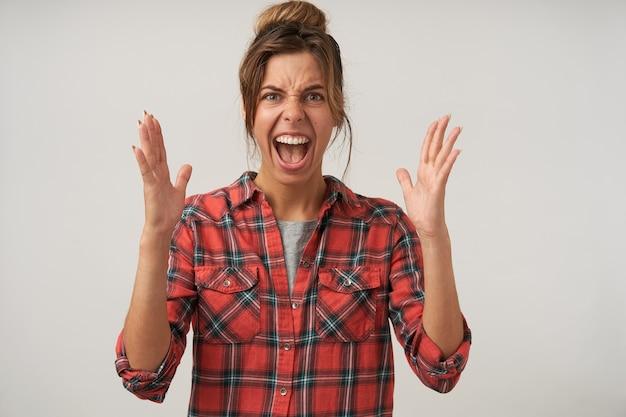 Retrato de uma jovem expressiva de cabelos castanhos com penteado casual, franzindo a testa enquanto grita e levanta emocionalmente as mãos, em pé sobre um fundo branco