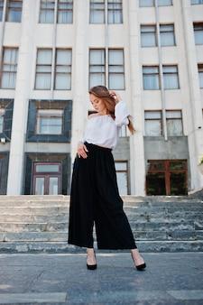 Retrato de uma jovem fabulosa e bem sucedida na blusa branca e calça preta larga, posando nas escadas
