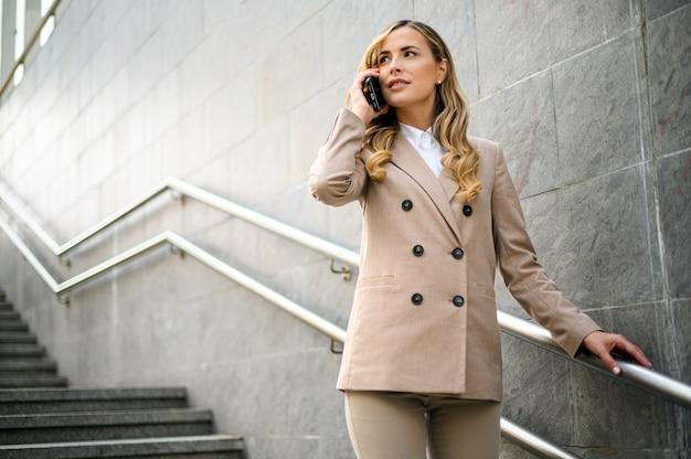 Retrato de uma jovem falando ao telefone na escada ao ar livre