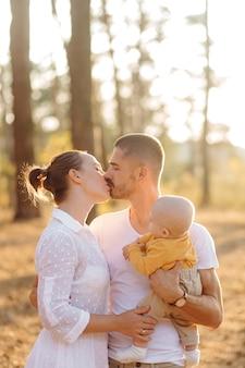 Retrato de uma jovem família atraente com filho pequeno, posando na bela floresta de pinheiros de outono em dia ensolarado. homem bonito e sua linda esposa morena