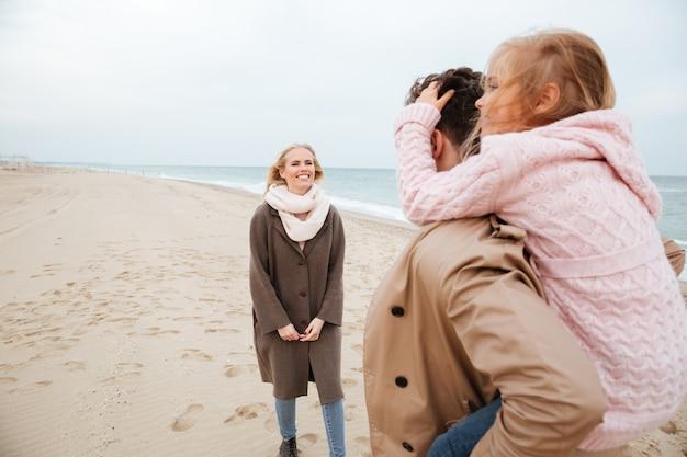Retrato de uma jovem família com uma filha pequena