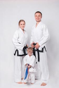 Retrato de uma jovem família feliz com uniforme de artes marciais em pé branco