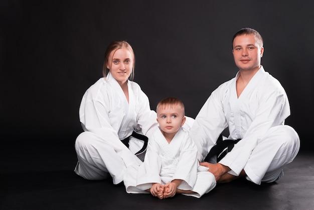 Retrato de uma jovem família feliz com uniforme de artes marciais em pé no preto