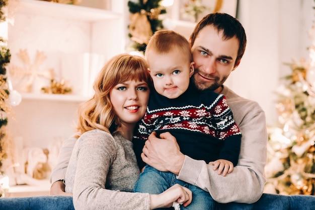 Retrato de uma jovem família feliz e alegre se divertindo em um sofá aconchegante com uma bola de natal dourada