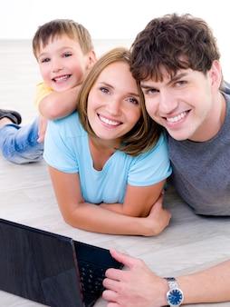 Retrato de uma jovem família feliz rindo com o filho pequeno e com laptop - dentro de casa