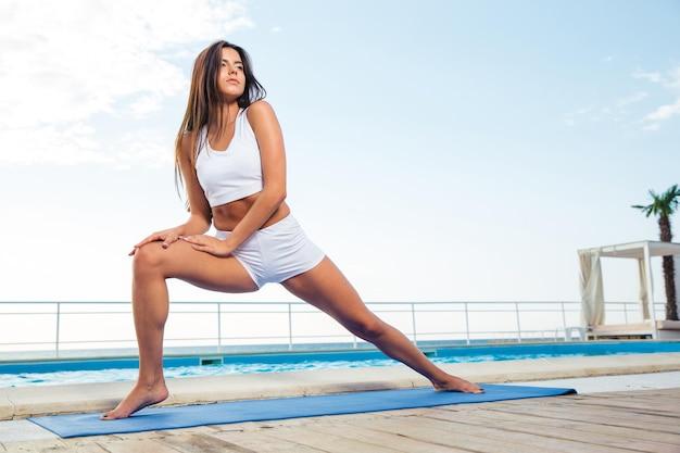 Retrato de uma jovem fazendo exercícios de alongamento ao ar livre pela manhã