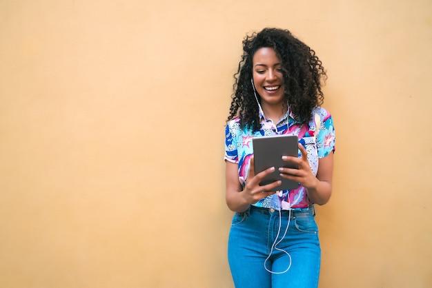 Retrato de uma jovem feliz afro-americana latina ouvindo música em seu tablet digital. conceito de tecnologia.