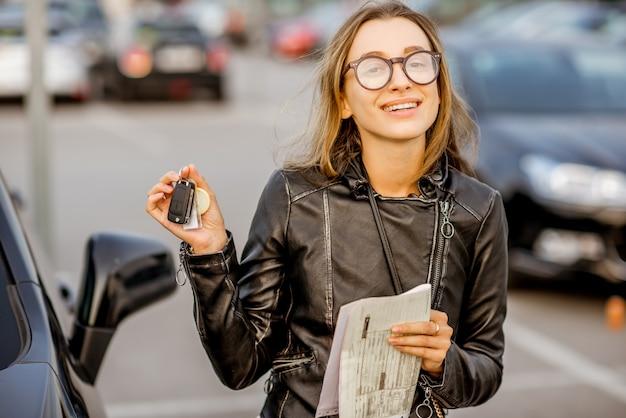 Retrato de uma jovem feliz com as chaves e o contrato de locação em pé perto do carro no estacionamento ao ar livre