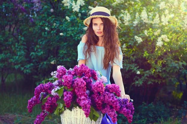 Retrato de uma jovem feliz com bicicleta vintage e flores no fundo da cidade à luz do sol ao ar livre.