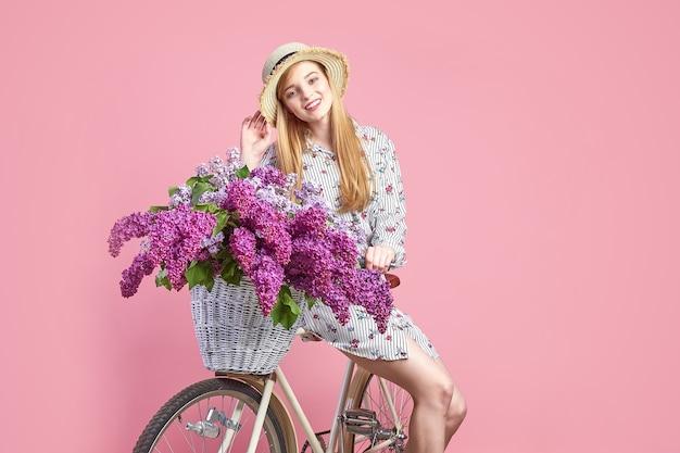 Retrato de uma jovem feliz com bicicleta vintage e flores sobre fundo rosa.