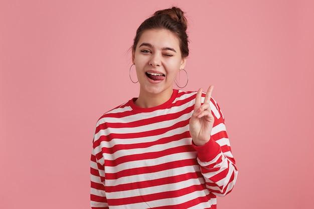 Retrato de uma jovem feliz com sardas, usa manga comprida listrada, pisca os olhos, mostra um gesto de paz e mostra a língua isolada sobre a parede rosa.