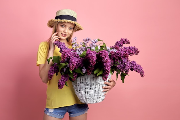 Retrato de uma jovem feliz com uma cesta cheia de lilás sobre fundo rosa.