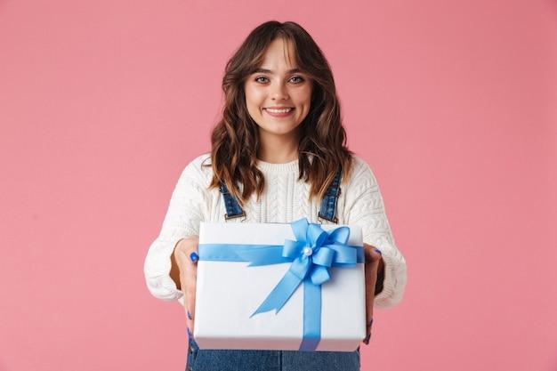 Retrato de uma jovem feliz dando uma caixa de presente