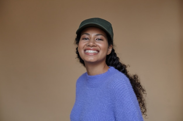 Retrato de uma jovem feliz, de pele escura, com seu cabelo castanho encaracolado trançado, parecendo alegre com um largo sorriso, vestida com roupas casuais e boné de beisebol