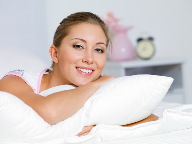 Retrato de uma jovem feliz descansando em uma cama em casa